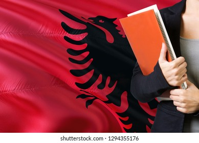 Learning Albanian language concept. Young woman standing with the Albania flag in the background. Teacher holding books, orange blank book cover.