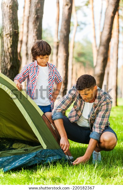 Learning the basics of camping. Cheerful father and son pitching a tent while camping in the forest together