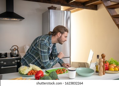 Learning to cook. A man watching video tutorials on cooking a salad