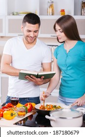 Learning to cook together. Happy young couple cooking together in the kitchen while man holding cookbook