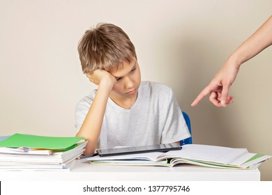 Learning difficulties. Angry mother pointing with hand that kid must do his homework instead of playing games on tablet