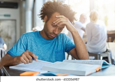 Learning and education. Indoor portrait of focused hardworking Afro American high school graduate preparing for college admission examinations and enrollement test, writing out notes from textbook