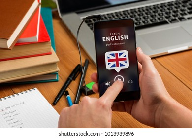 Learning English by listening. Student holding a phone with open podcast app. Laptop, books and dictionary notebook.