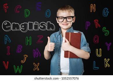 Learning English. Positive enthusiastic little boy looking happy and putting his thumb up while waiting for his favorite English lesson