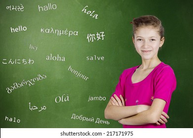 Learning foreign languages. Portrait confident teenager girl student standing by chalkboard with word hello written in different foreign languages. Education concept, international communication