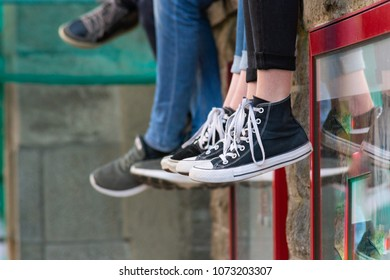 learning kids sitting on wall legs and shoes in focus