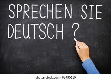 Learning language - German. Sprechen Sie Deutch (Do you speak German) written on blackboard. German language class concept showing teacher hand writing in German on chalkboard.