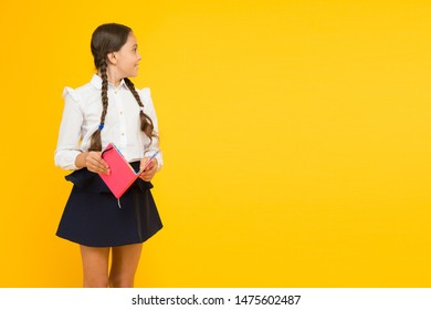 Learning language and literature. Cute small child holding book of childrens literature on yellow background. Little girl preparing for lesson of English literature. School literature, copy space.