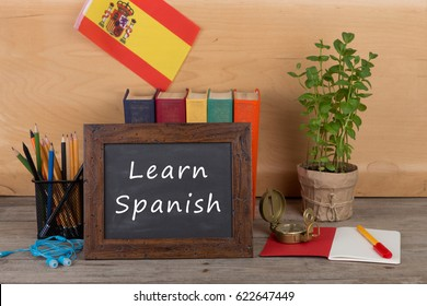 "Learning languages concept - blackboard with text ""Learn Spanish!"", flag of the Spain, books, pencils, compass on wooden background"