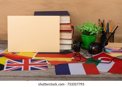 Learning languages concept - blank paper, flags, books, headphones, pencils on wooden background