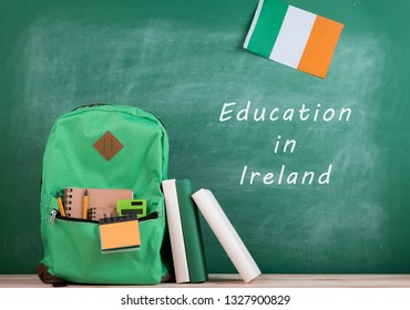 """Learning languages concept - green backpack, blackboard with text """"Education in Ireland"""", flag of the Ireland, books and notebooks"""