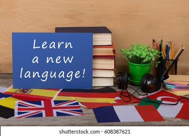 "Learning languages concept - paper with text ""Learn a new language!"", flags, books, headphones, pencils on wooden background"