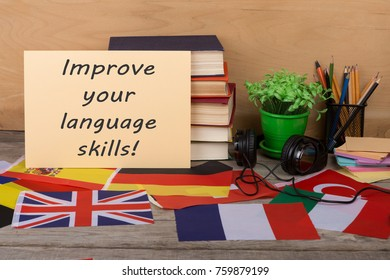 "Learning languages concept - paper with text ""Improve your language skills!"", flags, books, headphones, pencils on wooden background"