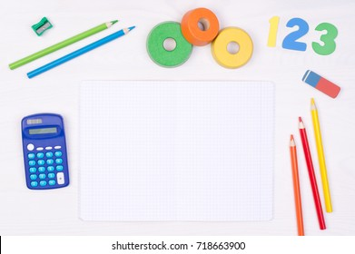 Learning maths. Kid's desk with blank notebook, colorful pencils, numbers and a calculator, top view with copy space