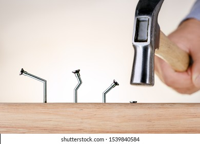 Learning from mistakes Businessman  hammering nails. Goal achievement.