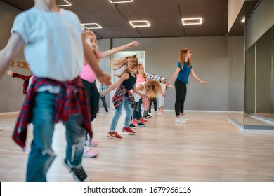 Learning modern dance. Happy boys and girls dancing with female dance teacher in the dance studio. Choreography concept. Sport. Active lifestyle