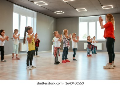 Learning a new dance. Group of little boys and girls dancing while having choreography class in the dance studio. Dance teacher and children. Contemp dance. Hip hop. Kids and sport. Full length