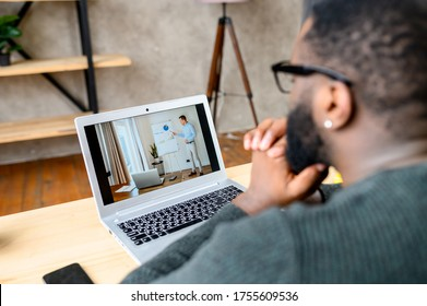 Learning online, webinar, online video classes. Focused African-American guy is watching online video lectures, male teacher with a flip chart on the laptop screen, view from the back.