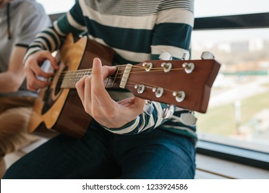 Learning to play the guitar. Interesting hobby or professional occupation of music. Music education or extracurricular activities or pastime