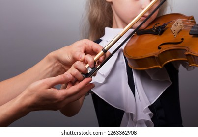Learning to play the violin. The little girl and the teacher plays the violin