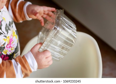 Learning to recycle concept: little baby-girl (toddler) throwing plastic container to recycling bin