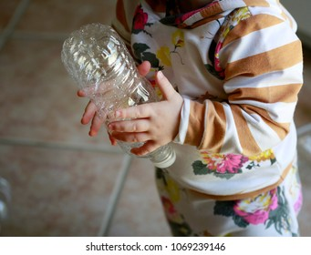 Learning to recycle concept: little baby-girl (toddler) carrying plastic bottle
