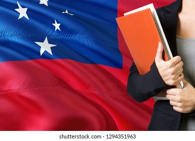 Learning Samoan language concept. Young woman standing with the Samoa flag in the background. Teacher holding books, orange blank book cover.