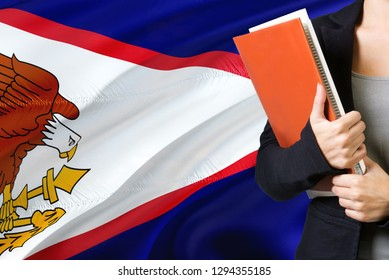 Learning Samoan language concept. Young woman standing with the American Samoa flag in the background. Teacher holding books, orange blank book cover.