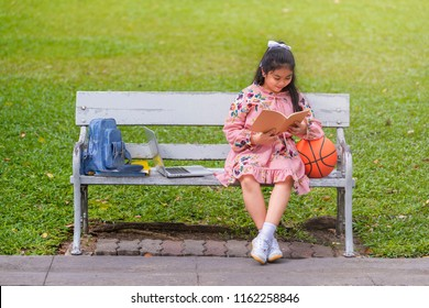 Learning, Sport Concept - Asian student girl sitting on a bench in a park and reading a book and near the girl is Basketball, Laptop and Backpack.