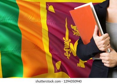 Learning Sri Lankan language concept. Young woman standing with the Sri Lanka flag in the background. Teacher holding books, orange blank book cover.