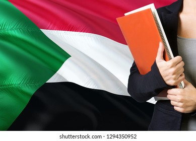 Learning Sudanese language concept. Young woman standing with the Sudan flag in the background. Teacher holding books, orange blank book cover.
