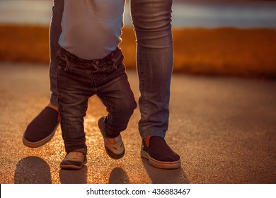 Learning to walk.Image of one year old baby boy having his first steps with the help of his mother.
