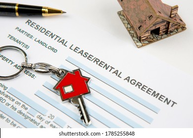 Lease agreement with new house key, model house and signature pen. Real estate, realtors, landlord, tenant and rental contract concepts. Horizontal close-up.