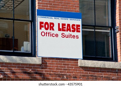 For Lease Office Suites blue and white sign on old brick office building between two windows. Room for your text on sign.
