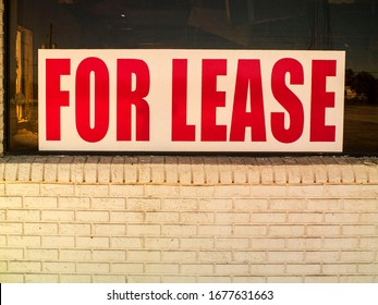 For Lease Red Letters with White Background on the Front Window of an empty Store. Empty Storefront with a For Lease Sing on the Window.