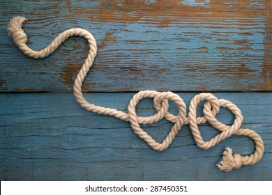 leash  rope into heart shape on wooden table