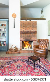 Leather armchair in cozy room with red brick fireplace