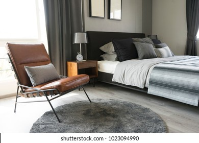 leather armchair and gray carpet in bedroom