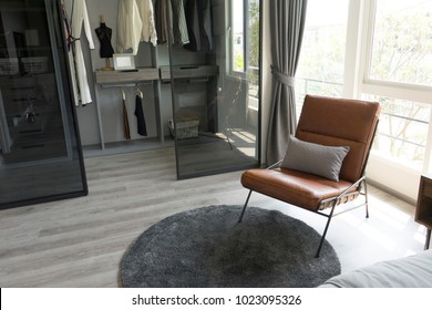 leather armchair and gray carpet near walk in closet