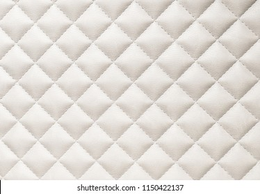 leather background. A closed up details of a beige leather paded upholstery pattern texture.