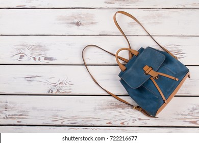 Leather backpack with thin straps on wooden background. Blue and light brown. Fashionable garments for carrying essentials.