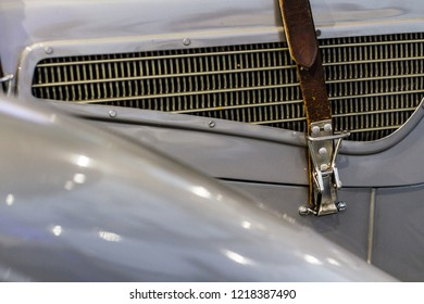 Leather belt on vintage oldtimer gray car on radiator grill