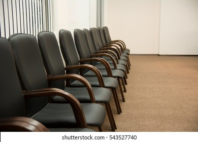 Leather black chairs are standing near the wall in a room with shutters on the windows