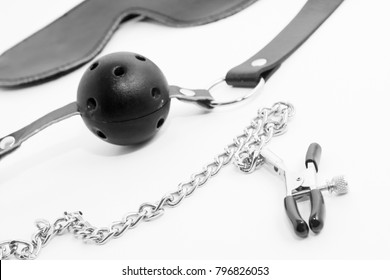 Leather blindfold with gag and nipple clamps isolated on a white background