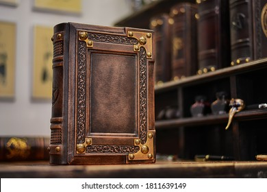 Leather book over wooden table, books in the background and pictures on the wall