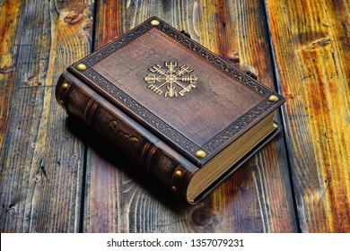 Leather book with the Vegvisir, ancient Icelandic magical symbol. The book is captured from the left side while lay down to the aged wooden table