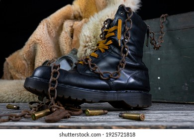 Leather boot with rusted chains and bullet shells with military gas mask and fur coat in background resting on wooden table