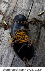 Leather boot with rusted chains and bullet shells resting on wooden table