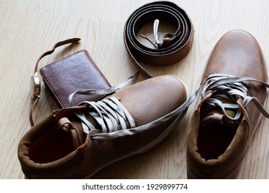Leather boots, belt, wallet and watch on a wooden surface. Closeup