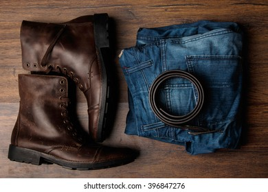 Leather boots, jeans and belt on wooden surface